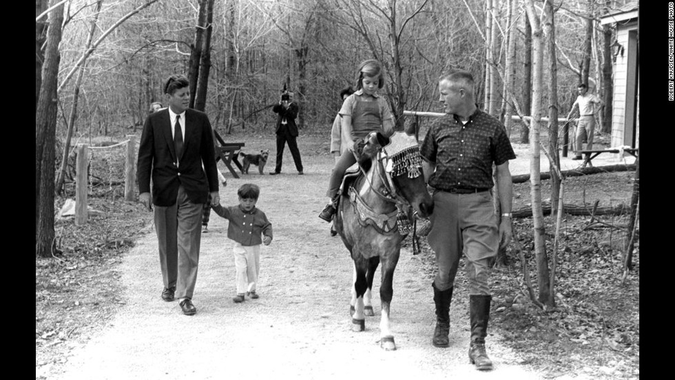 President Kennedy and his son walk holding hands as Caroline rides Macaroni.