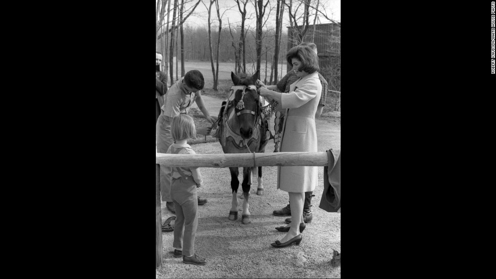 Jackie Kennedy helps get Macaroni harnessed and saddled for Caroline.