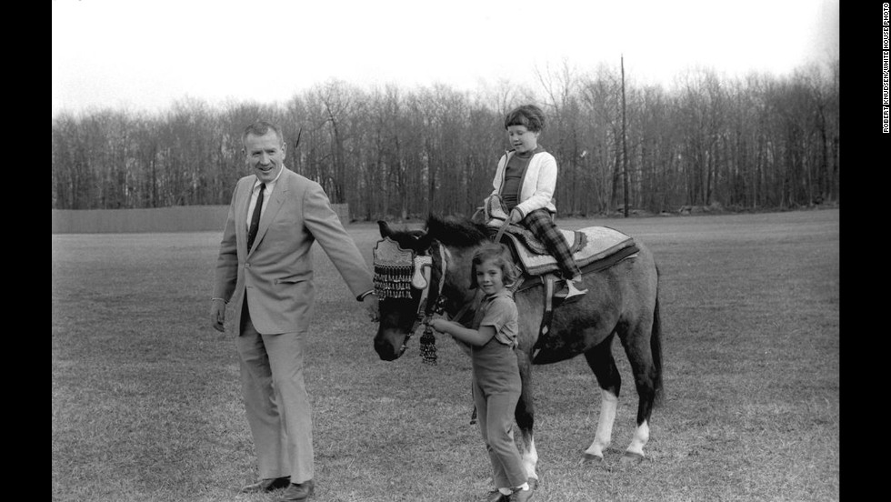 Sally Fay sits on Macaroni as her father and Caroline Kennedy hold the bridle.