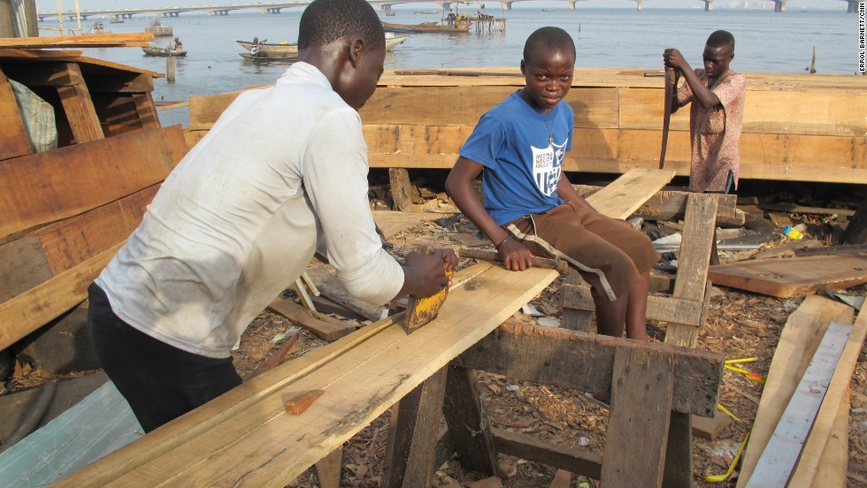 Young men in Makoko are typically put to work building canoes, in business ventures supervised by elders. Here, one teen sits on a plank of timber as two others work to saw it into pieces.