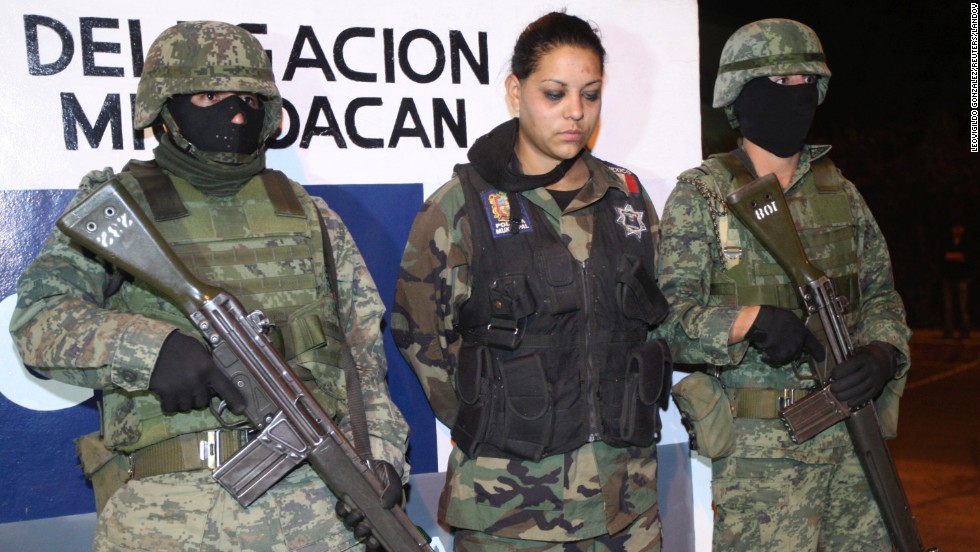 Suspect Erika Garcia, a police officer, is presented to the media after she was arrested by troops in Uruapan, on February 27, 2011. Garcia was arrested after soldiers stopped a convoy of three luxury vehicles carrying her and suspected drug traffickers at a military checkpoint, according to local media.