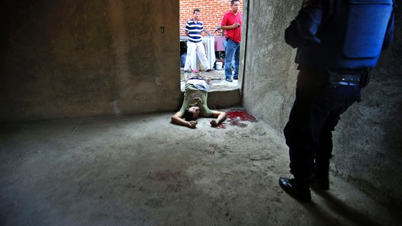 Police walk near a victim of a shootout between the drug cartels La Familia and Los Zetas in Uruapan  on December 14, 2009.