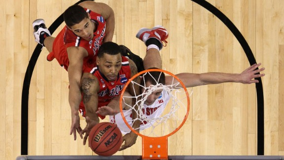 Nick Johnson, left, and Mark Lyons, center, of the Arizona Wildcats battle Aaron Craft of the Ohio State Buckeyes for a rebound on March 28 in Los Angeles.