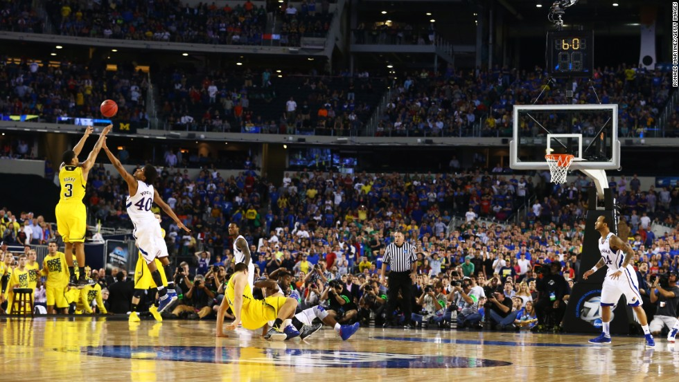 Trey Burke of the Michigan Wolverines shoots a game tying three-pointer in the final seconds of the second half over Kevin Young of the Kansas Jayhawks on March 29 in Arlington, Texas.