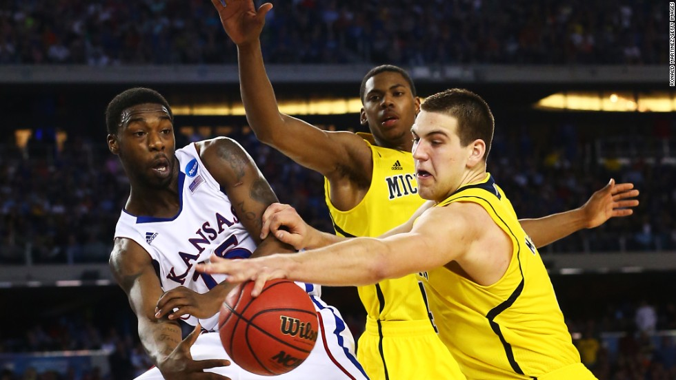 Mitch McGary of Michigan, right, blocks a pass from Elijah Johnson of Kansas in overtime on March 29.