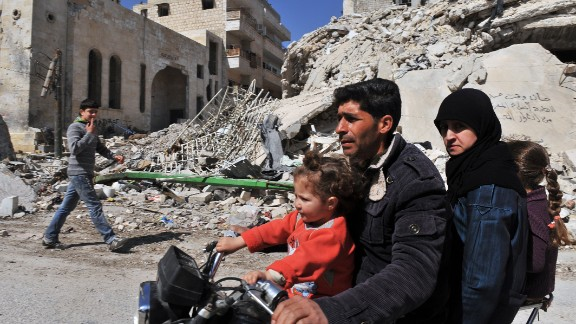 A Syrian man and his family drive past damaged buildings in Maarat al-Numan, on Wednesday, March 20.