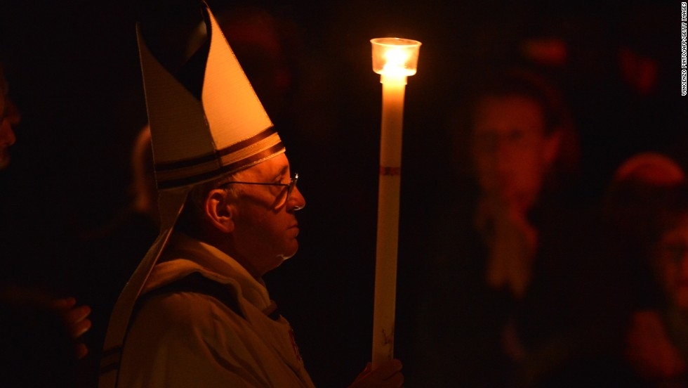 Pope Francis holds a candle during the Easter Vigil on Holy Saturday at St. Peter's Basilica on Saturday, March 30 at the Vatican. Francis is taking part in his first Holy Week as pontiff.