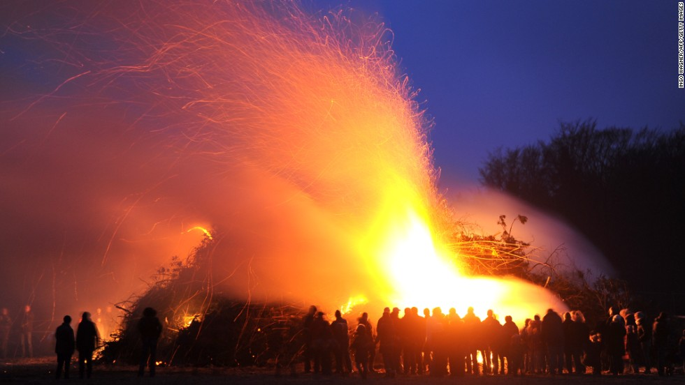 People stand by an Easter fire on Saturday, March 30, in Hellwege, Germany.