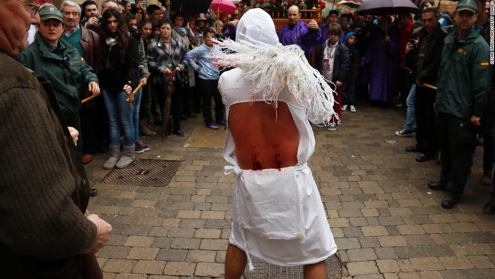A penitent whips himself during the Santa Vera Cruz brotherhood procession for Holy Week in San Vicente de la Sonsierra, northern Spain, on Friday.