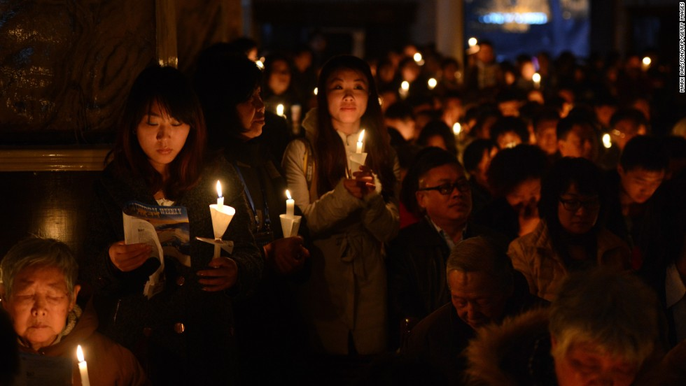 Chinese Catholics hold candles as they pray at the Cathedral of the Immaculate Conception in Beijing on Saturday.