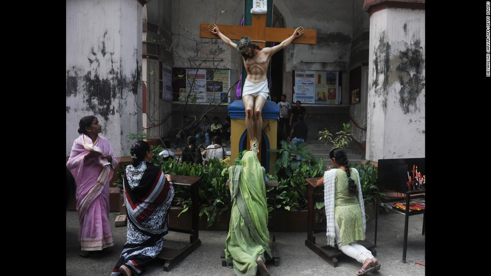 Christians pray in front of a statue of Jesus Christ at a church in Kolkata, India, on Friday.