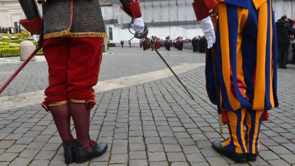 Swiss guards stand in St. Peter's Square before the Easter celebrations on Sunday.