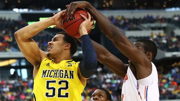 Patric Young of Florida blocks a shot by Jordan Morgan of Michigan.