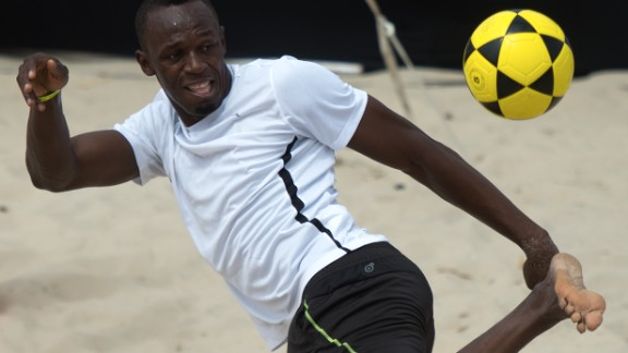 """Usain Bolt plays """"foovolley"""" in a promotional event at Copacabana beach in Rio de Janeiro ahead of his 150m race."""