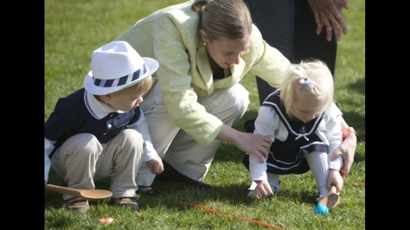 A woman helps young children in the race.