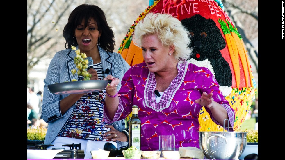 Michelle Obama watches chef Anne Burrell cook.