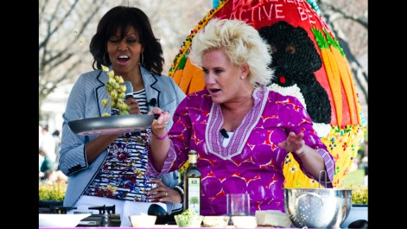 Michelle Obama watches chef Anne Burrell cook.