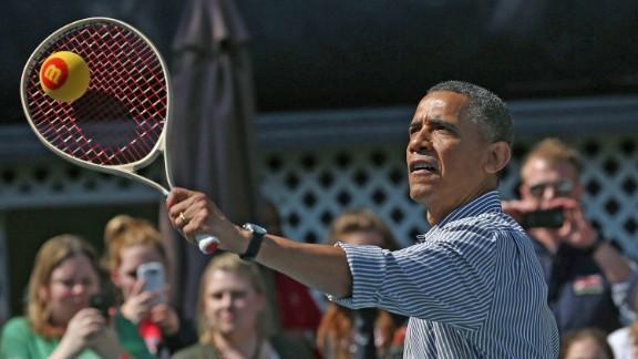 Obama plays tennis with children.