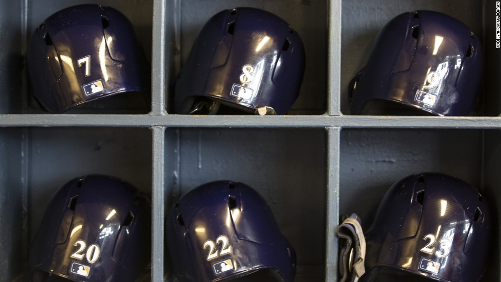 Batting helmets sit on shelves in the Milwaukee Brewers' dugout during the game against the Colorado Rockies.