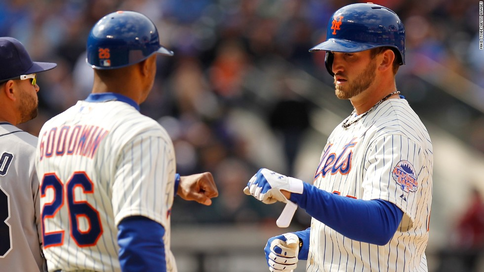 Jonathon Niese of the New York Mets, right, is congratulated by first-base coach Tom Goodwin after hitting a single.