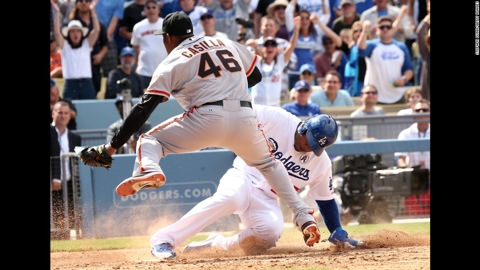 Carl Crawford of the Los Angeles Dodgers slides into home under pitcher Santiago Casilla of the San Francisco Giants.