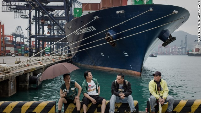 Dockers sit in front of a ship at the Kwai Chung container terminal in Hong Kong on March 29.