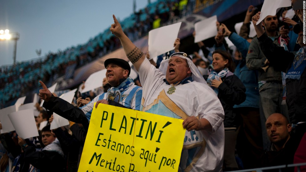 Malaga fans protest against UEFA president Michel Platini over threats to refuse the club permission to play in European competition next season because of its financial situation.