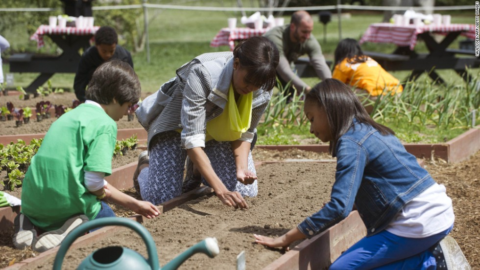 First lady Michelle Obama and a group of students from across the country planted the White House Kitchen Garden on the South Lawn on Thursday, April 4. Emilio Vega of Bradenton, Florida, left, and Ariana Docanto of Somerville, Massachusetts, plant wheat alongside the first lady.