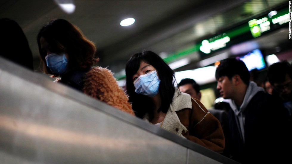 A woman wears a face mask inside a subway station in Shanghai, China, on Friday, April 5. The Chinese minister of agriculture said Thursday it had discovered the H7N9 virus in samples taken from pigeons at Huhai agricultural market, China's state-run Xinhua news agency reported.
