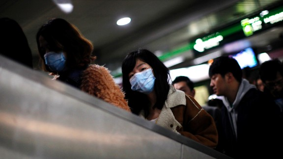 A woman wears a face mask inside a subway station in Shanghai, China, on Friday, April 5. The Chinese minister of agriculture said Thursday it had discovered the H7N9 virus in samples taken from pigeons at Huhai agricultural market, China