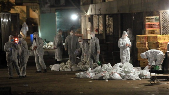 Chinese health workers collect bags of dead chickens at the Huhai wholesale market on April 5.