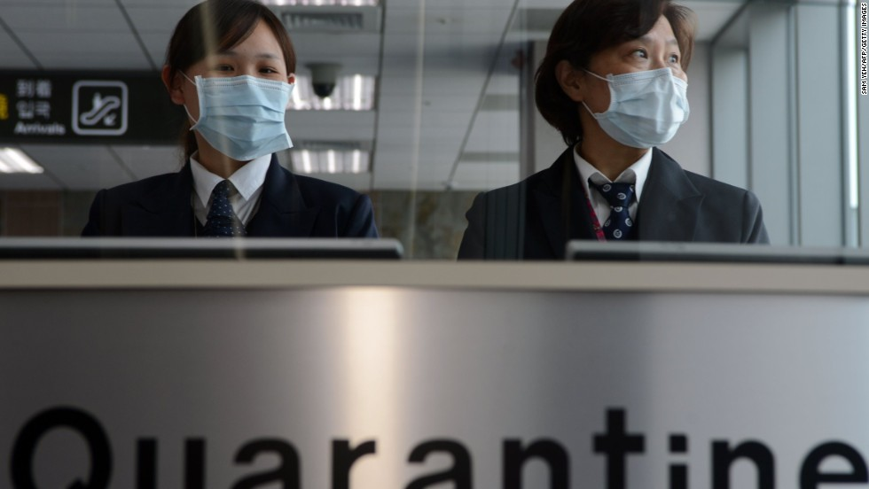 Staff members from Taiwan's Center for Disease Control stand at the entrance of Sungshan Airport in Taipei.