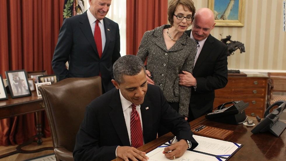President Obama signs the Ultralight Aircraft Smuggling Prevention Act as Vice President Joe Biden, Giffords and her husband look on in the Oval Office of the White House on February 10, 2012. The bill was the last piece of legislation Giffords voted on before she resigned.
