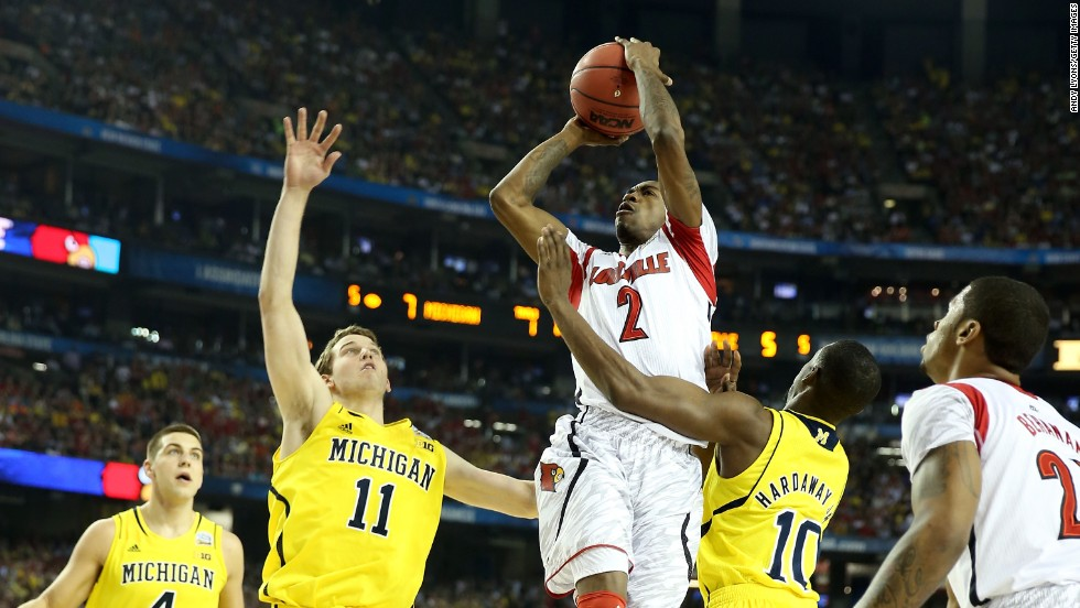 Russ Smith of Louisville drives for a shot in the first half against Nik Stauskas, left, and Tim Hardaway Jr., right, of Michigan.