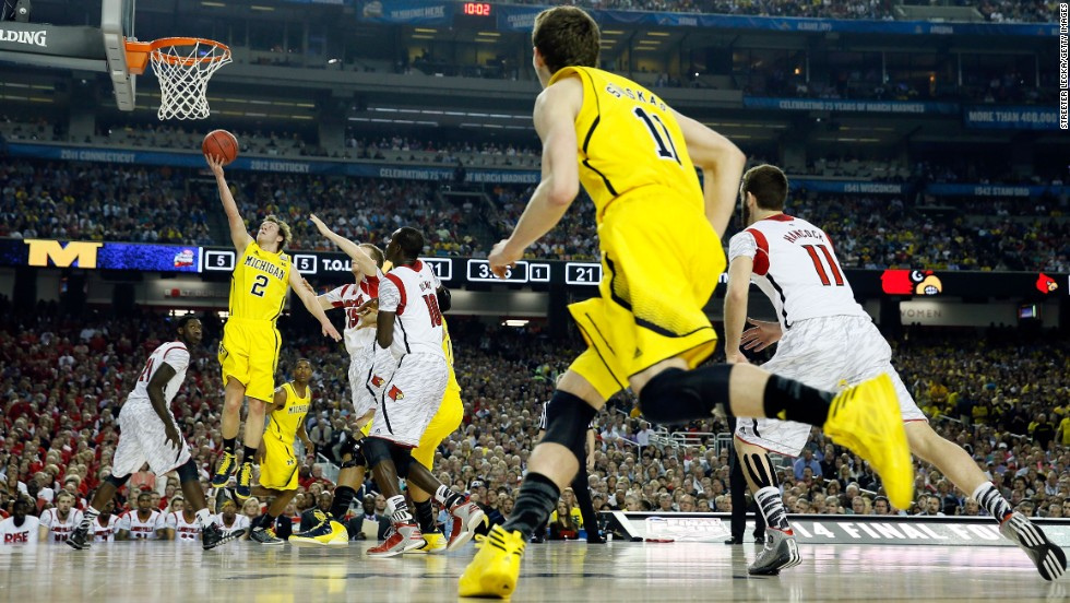 Spike Albrecht of the Michigan Wolverines drives for a shot in the first half against the Louisville Cardinals.