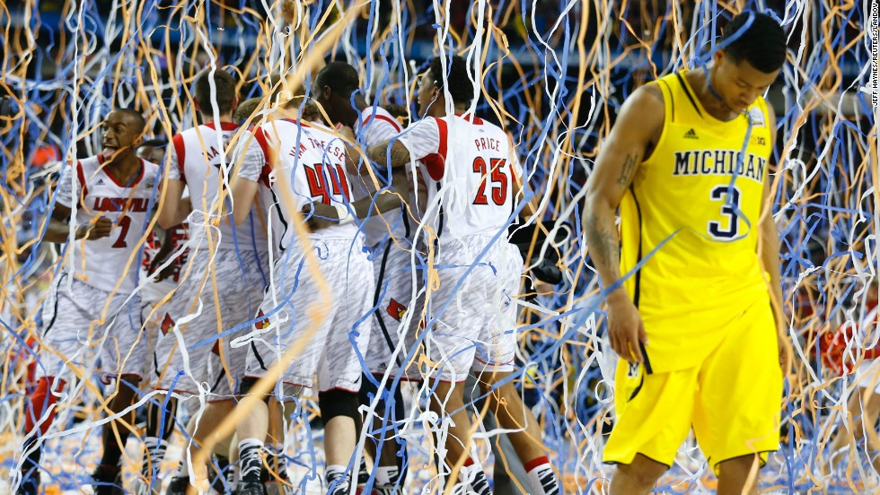 Trey Burke of Michigan walks off the court as the Louisville Cardinals celebrate.