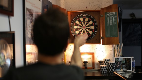 Staffers and interns play darts during some downtime on the weekend shift at CD102.5.