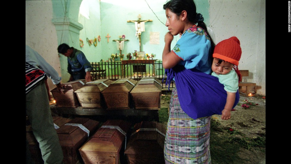 A grieving mother stands over the remains of her daughter at a church in Rabinal, Guatemala, in 2002. Coffins bearing victims' remains were brought to the church months after archaeologists found and exhumed the bodies based on witness testimony.