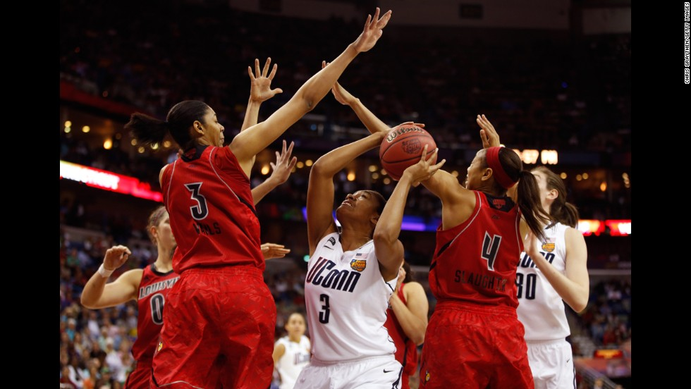 Morgan Tuck of UCONN handles the ball under the basket against Sheronne Vails, left, and Antonita Slaughter, right, of Louisville on April 9.