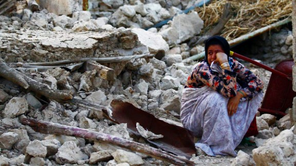 A woman sits among the wreckage in Shanbeh in Bushehr province on April 9.