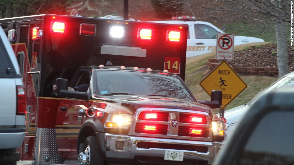 "A Gwinnett County Fire Rescue ambulance rushes from the scene after the hostage situation ended. The four firefighters being held hostage suffered ""superficial"" injuries as a result of the explosions."