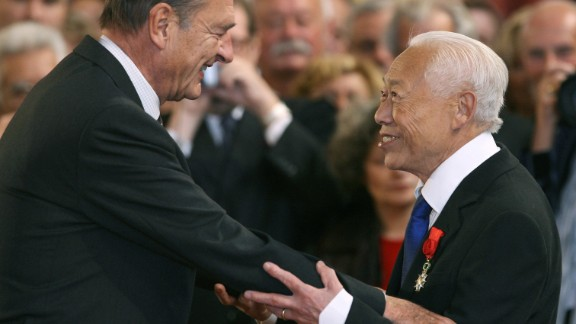 French President Jacques Chirac (L) gives the insignia of the