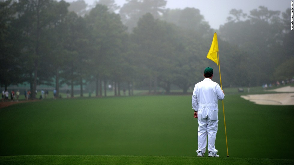 A caddie stands near the first hole before the start of the first round.