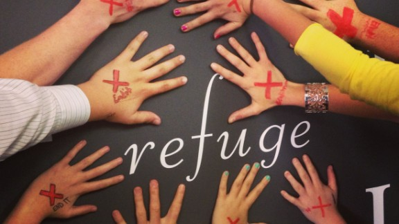 """Katelyn Boyd, a high school Bible teacher, and her students circled their hands around the word """"Refuge,"""" which is part of a mural wall in their classroom. """"I wanted to make my high school students aware of the fact that slavery still exists and that THEY can do something to stop it...right now, where they are,"""" she says."""
