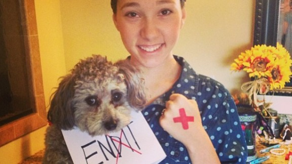 """Katy Duke and her dog Daisy Jo Duke are in it to end human trafficking. She says her heart breaks for the 27 million people in the world who are bound to slavery through sex trafficking. """"I believe that by simply drawing a red X on my hand could raise awareness and one day change the world, but I cannot do it alone,"""" Duke says."""