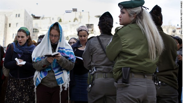 "An Israeli border policewoman stands guard as members of the liberal religious group ""Women of the Wall"" wear tallits, Jewish prayer shawls worn by men, while praying at the Western Wall in Jerusalem's Old City."