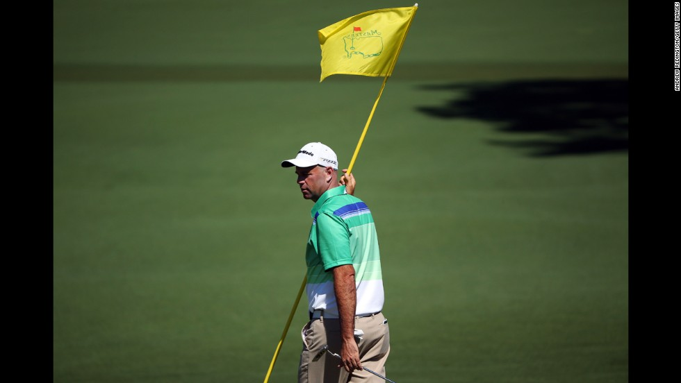 Stewart Cink of the U.S. holds the flag on the second hole.