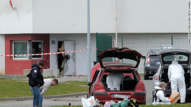 Forensics experts work near a door destroyed by Faid's explosives in 2013.