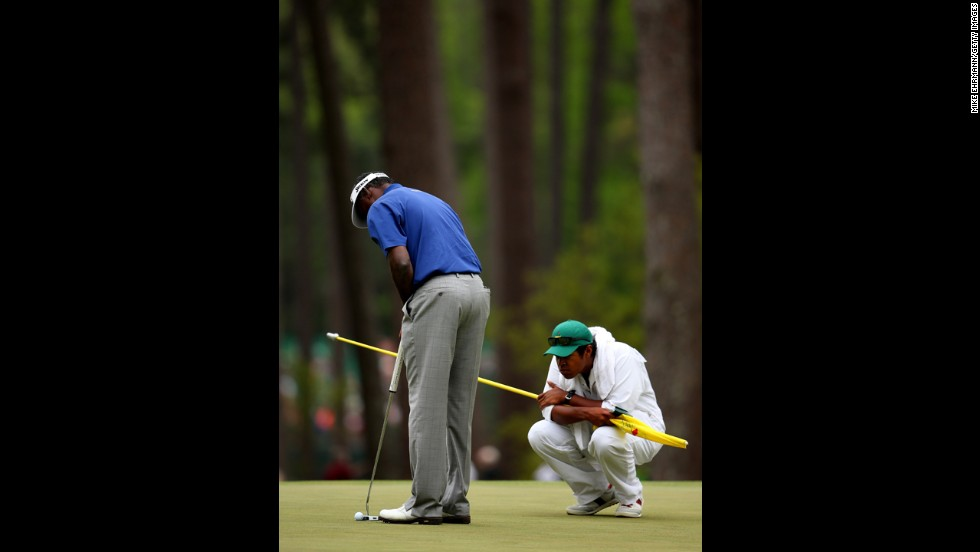 Vijay Singh of Fiji putts as his caddie watches on the third hole.