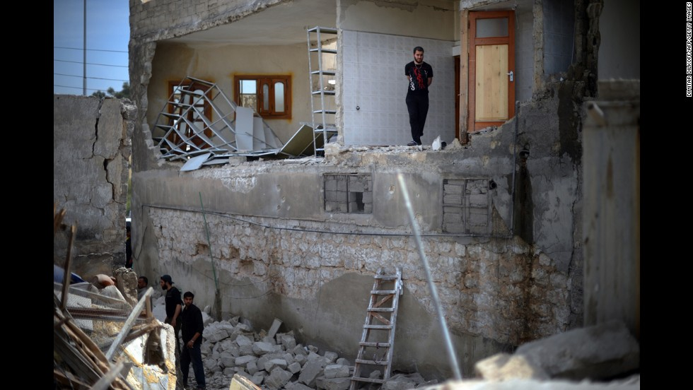 Men inspect damage at a house destroyed in an airstrike in Aleppo on April 15.